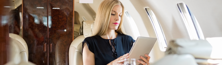 a businesswoman connecting to inflight internet from the Gogo Ku global network