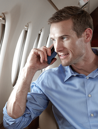 a businessman taking a phone call during a flight