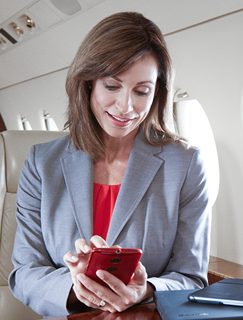 a businesswoman texting on a smartphone during a flight