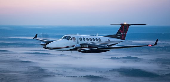a King Air turboprop aircraft flying above the clouds
