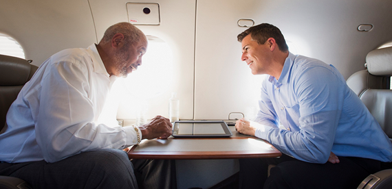 two colleagues using inflight wifi to discuss business plans