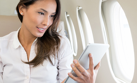 a VVIP passenger using inflight wifi on a tablet